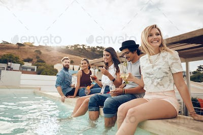 Young people hanging out by swimming pool