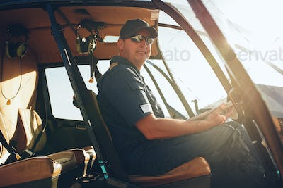 Happy male pilot in a helicopter cockpit
