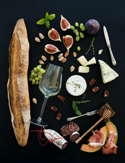 Wine and snack set. Baguette, glass of white, figs, grapes, nuts, cheese variety, meat appetizers