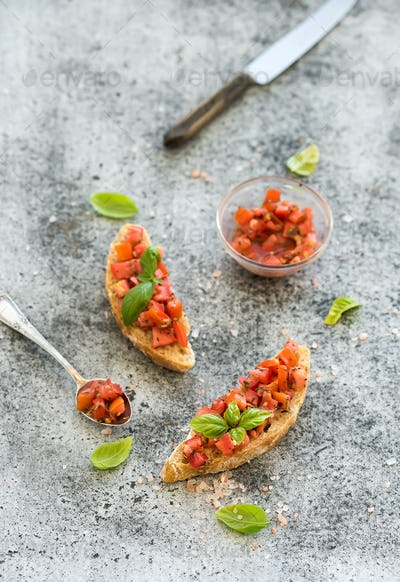 Tomato and basil bruschetta sandwich over grunge gray background, top view.