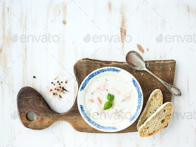 Scandinavian salmon soup with cream, fresh basil and bread in vintage ceramic plate