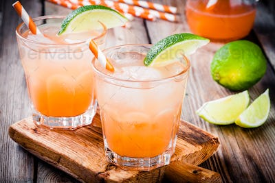 Tequila sunrise cocktail with ice and lime