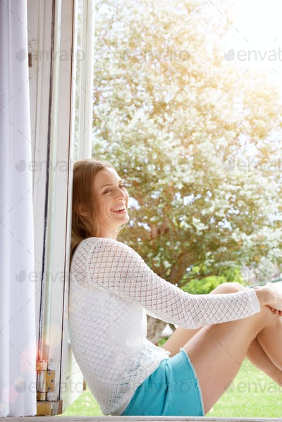 Attractive woman sitting and smiling at home