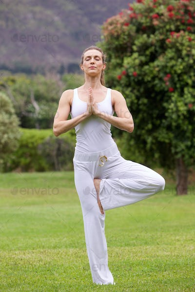 Yoga woman standing on one leg in park