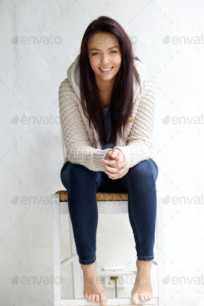 Smiling young woman sitting on chair
