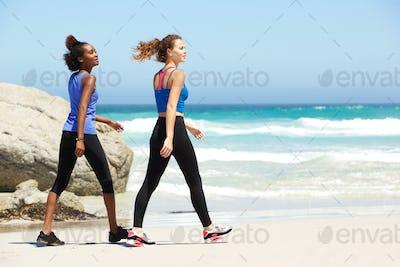 Two young sporty women walking on beach