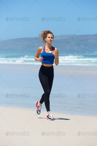 Full length active young woman running on beach