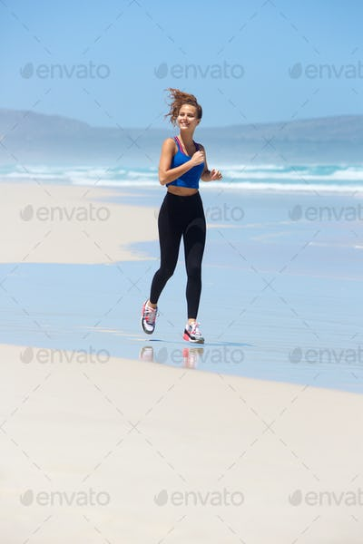 Smiling young woman running on beach