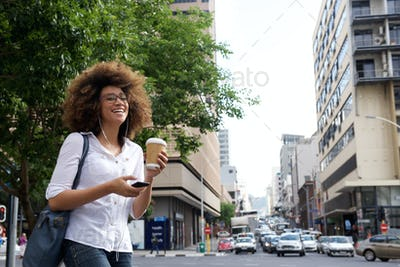 Cheerful woman walking in the city with cell phone