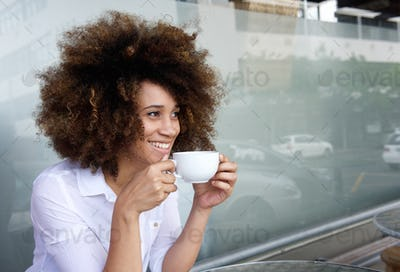 Smiling african american woman sitting with cup of coffee