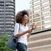 Smiling african woman walking and laughing with cell phone