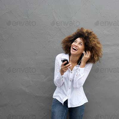 Laughing young woman listening to music on cell phone