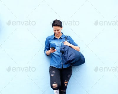 Cool young woman smiling with mobile phone and bag