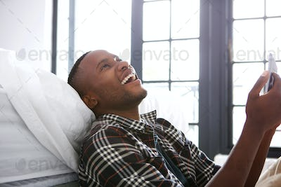 Cheerful young african man sitting at home with a digital tablet