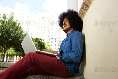 Smiling black guy sitting outside with laptop