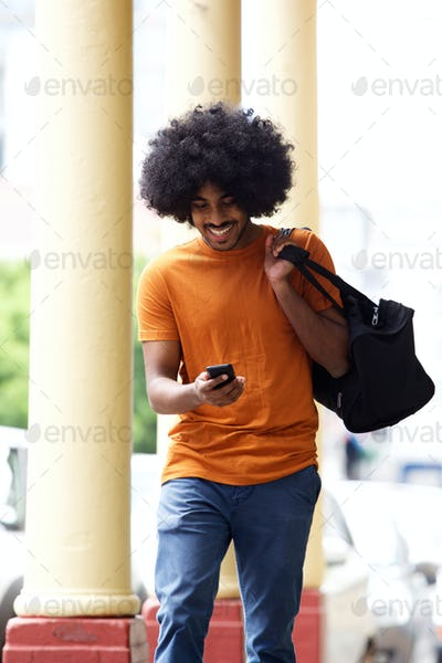 Happy man with bag looking at cellphone in the city