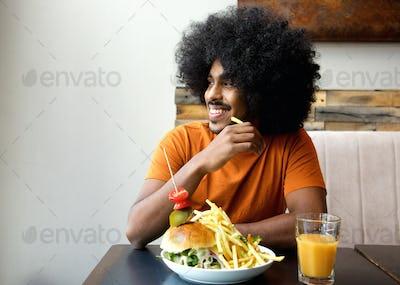 Smiling man with hamburger and fries at restaurant