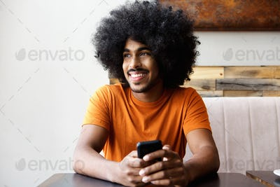 Smiling african american man sitting at table with mobile phone