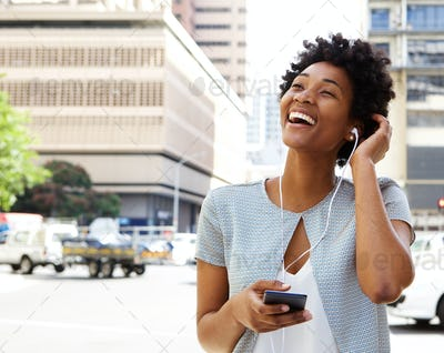 Smiling young woman listening music on headphones