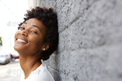 Happy young african woman leaning to a wall