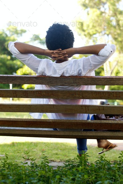 Relaxed young woman sitting on a park bench