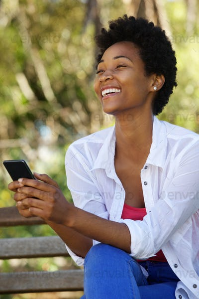Cheerful young woman sitting on a bench with a mobile phone