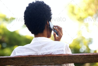 Woman sitting on a park bench and talking on mobile phone