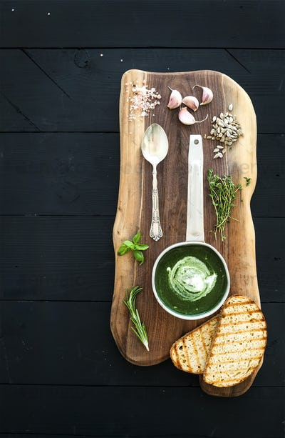 Homemade green spinach cream-soup in a metal scoop with grilled bread slices, herbs, spices