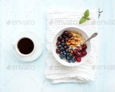Healthy breakfast set. Bowl of oat porridge with fresh berries, almond and honey