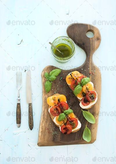 Tomato, mozzarella and basil sandwiches on dark wooden chopping board, pesto jar, dinnerware