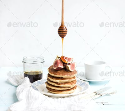 Pancake tower with fresh figs and honey on a rustic plate. White background