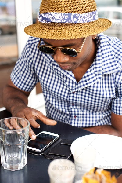 Cool african american man sitting at a cafe using mobile phone