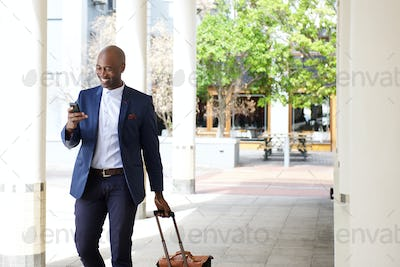 Businessman traveling with a bag and mobile phone