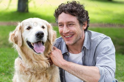 Smiling man with his dog in park on a sunny day