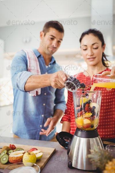 People preparing fruit juice at table in home