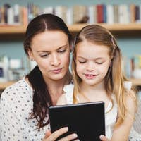 Close-up of mother and daughter using digital tablet on sofa at home