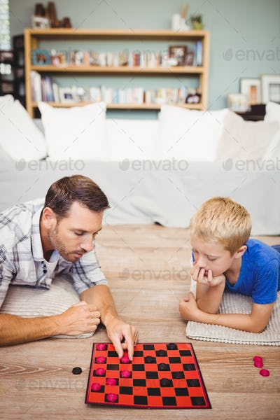 Father and son playing checker game while lying on floor at home