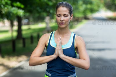 Sportswoman meditating with hands joined in park