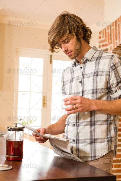 Handsome man reading the news and having coffee in the kitchen