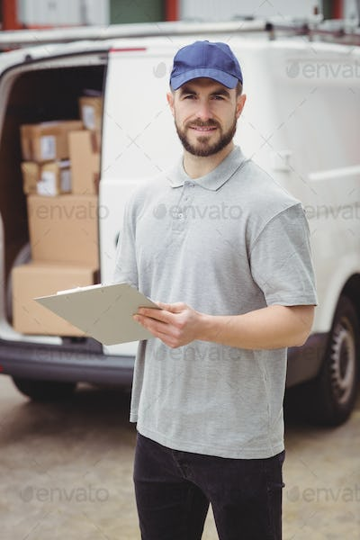 Delivery man holding clipboard in front of his van