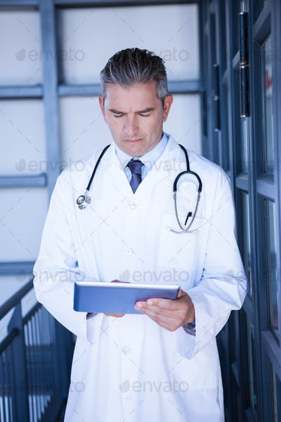 Serious male doctor using digital tablet in the hospital