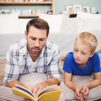 Close-up of father and son reading book while lying on floor at home
