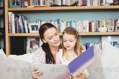Close-up of mother and daughter reading book on sofa at home