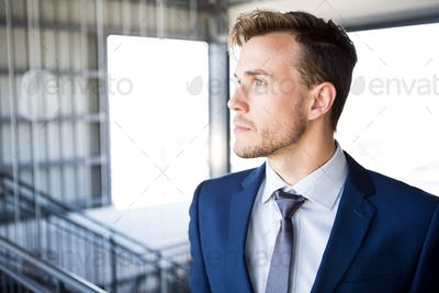 Businessman looking away and thinking in office