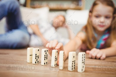 Close-up of girl arranging domino on floor at home