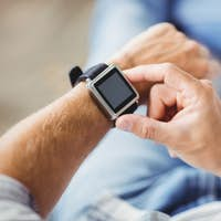 Midsection of man wearing smart watch at home