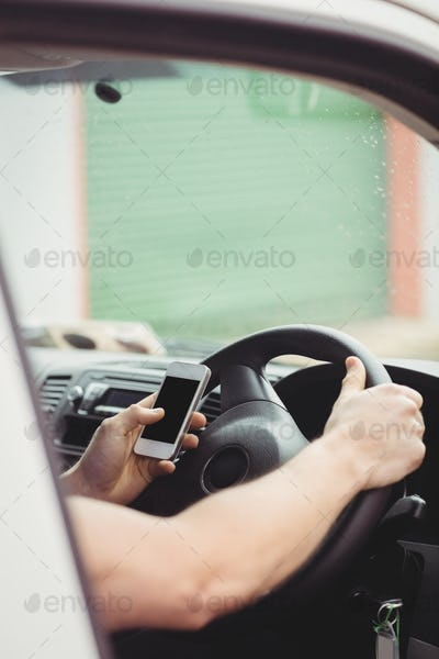 Delivery man driving his van while using smartphone
