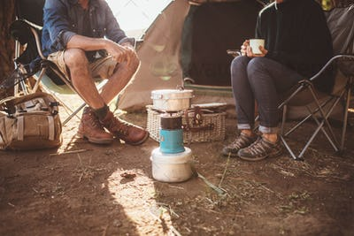 Mature couple sitting around a camp stove at campsite