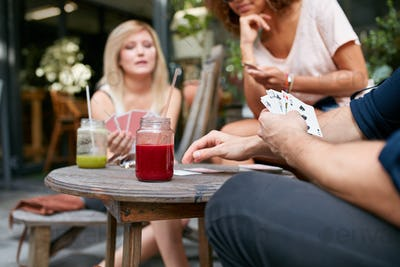 Friends sitting at outdoor cafe playing card game