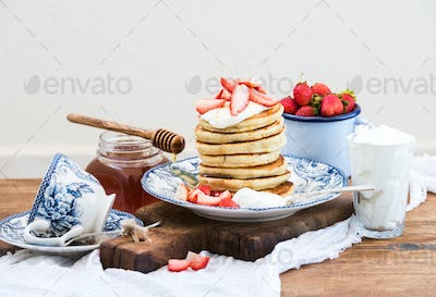 Breakfast set. Pancakes with fresh strawberries, sour cream and honey